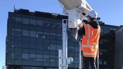 man checking for solar cameras for security guard services